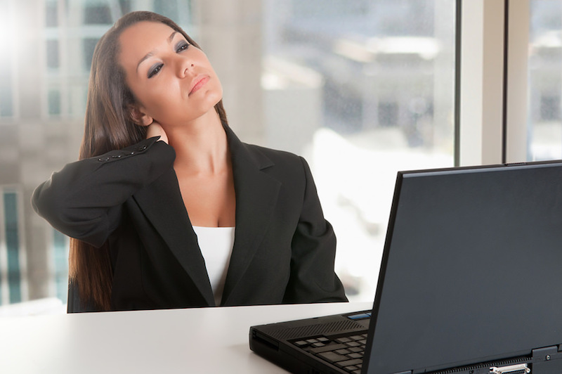 Business woman grabbing back of neck in pain, at computer