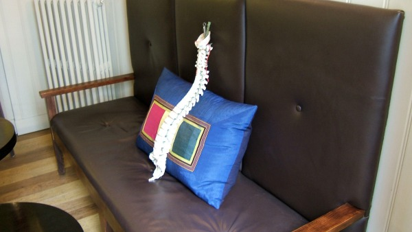 Positioning a bulky pillow in the  small of the back prevents the spine slumping into a C-bend during relaxed sitting.
