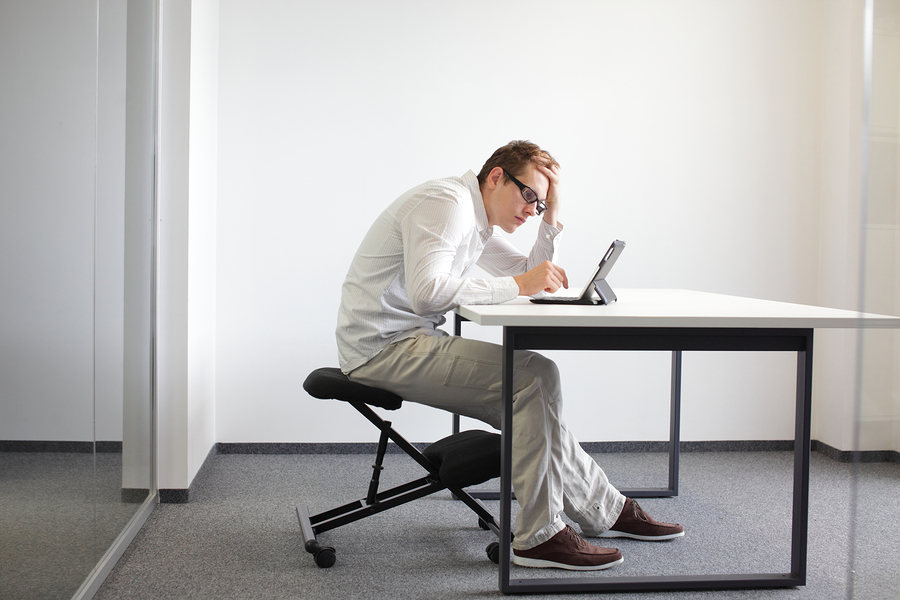 Stooped computer posture, man sitting at a desk in front of a computer