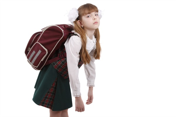 Though children may complain, heavy school bags help develop core strength and postural tone